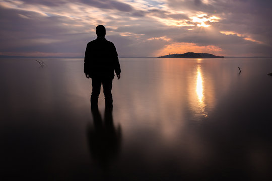 Long exposure shot of a silhouette of a man in water in front of a sunset