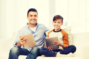 happy father and son with tablet pc at home