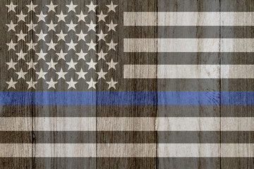 A rustic old thin blue line flag on weathered wood