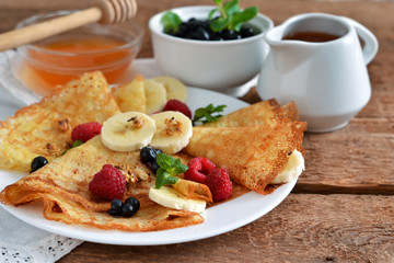 Homemade pancakes with banana, berries and honey for breakfast on a wooden background