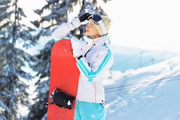 Young beautiful girl in white jacket, blue ski pants and googles on her head standing with snowboard in the snowy mountain forest. Winter sports.