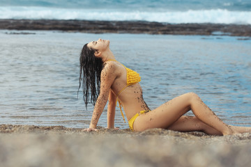 Pretty girl in sexy yellow swimsuit sitting on sandy beach