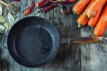 Black empty cast-iron frying pan among vegetables