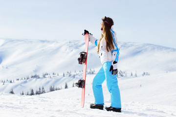 Young beautiful girl in white jacket, blue ski pants and googles on her head standing with snowboard in the snowy mountains. Winter sports.