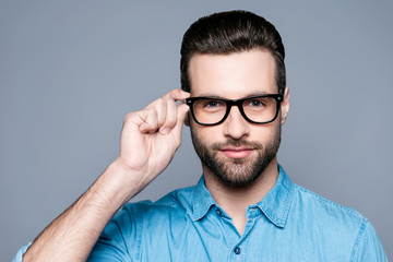 A portrait of young handsome man in jeans shirt  isolated on gray background touching his glasses