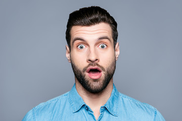 A close up portrait of a young surprised man with opened mouth isolated on gray background