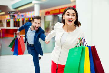 Hurry faster! It's shopping time and fun. Handsome cheerful  successful happy  man  holding hands and following his lovely cute woman with colored shopping packages and laughing in mall at holiday.