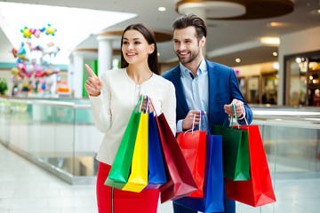 Cute cheerful  successful happy lovely couple in jacket holding colored shopping packages, pointing and looking on shop  and laughing in mall at holiday. It's shopping time with  sales and fun.