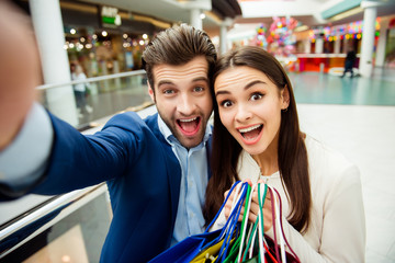 It's shopping time with crazy sales and fun. Selfie portrait of cheerful  successful happy young lovely couple surprised holding  colored shopping bags and laughing in mall at holiday