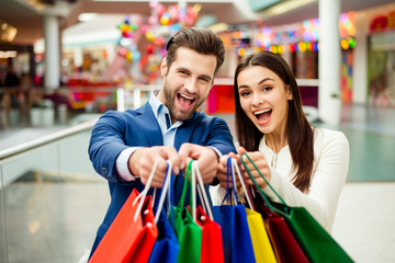 It's shopping and fun  time. Portrait of cheerful  successful happy young lovely couple holding  colored shopping bags and laughing in mall. Concept of consumerism, sale, rich life and people