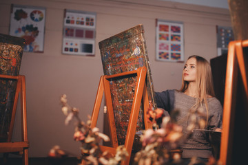 Artist beautiful girl paints a picture on canvas with watercolor in her workshop and art school.