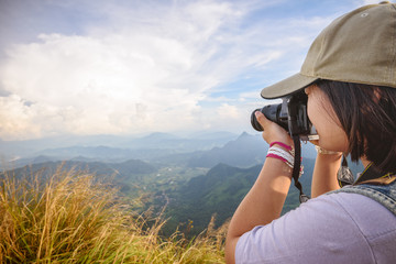 Side face of hiker teens girl wear caps with digital camera taking photo beautiful landscape natural of sierra and sky on mountain at viewpoint Phu Chi Fa Forest Park, Chiang Rai, Thailand
