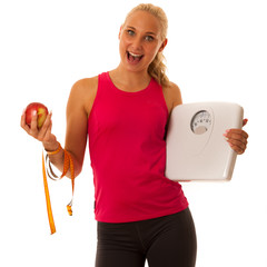 Fit blonde woman holding scale gesturing healthy lifestyle and weight lose