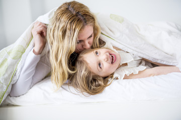 Cute little girl and her mother kiss lying on a bed