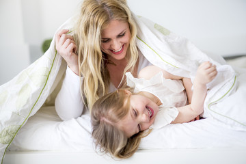 Cute little girl and her mother lying on a bed