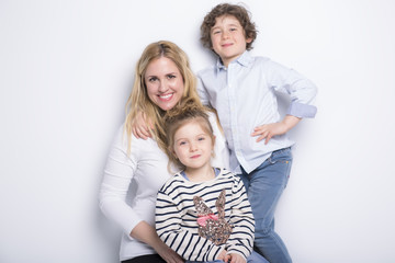 mother, her son and daughter in front of white background