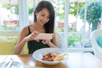 Woman taking photo with cellphone on her dish in restaurant
