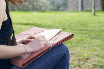 Young brunette woman artist, drawing sketch and thinking, looking for inspiration. Outdoors, in nature.
