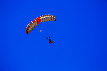 Skydiving with a Red Parachute on a Blue Sky