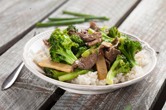 Beef N' Broccoli Stir Fry on light weathered wood with green beans to side horizontal shot