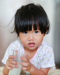 Close up of little girl in pajamas drinking milk from glass indoor at the morning.