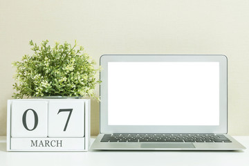 White wooden calendar with black 7 march word with white blank space at center of computer notebook on white wood desk and cream wallpaper textured background , selective focus at the calendar