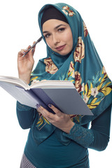 Female student author or journalist writing notes on a book with a pen.  She is wearing a hijab associated with muslims or middle eastern and east european culture.