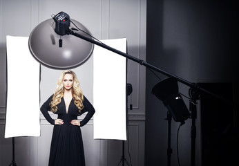 Beautiful and attractive model in black dress. Backstage shooting. Fashion, beauty, glamour concept.