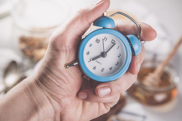 Morning alarm concept - hand with clock