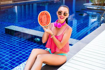 A beautiful, cheerful girl sits by the pool with half a red watermelon, laughs and listens to music in large pink headphones, a bright bikini, sunglasses, rest at the hotel, a suntanned perfect body.