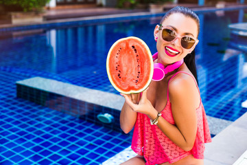 Close-up portrait of a happy cute girl holding half a red watermelon and laughing, smiling and listening to music in large pink headphones. Vacation on a tropical island, perfect smile, white teeth
