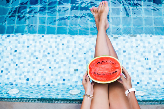A girl holds half a red watermelon stretching long, tanned legs over a blue pool, relaxing on a tropical island in a hotel, eating healthy, fruit diet, summer style