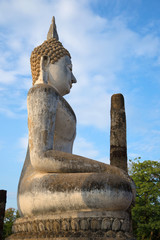 Ancient sculpture of a seated Buddha at the ruins of the temple Wat Chana Songkhram in the evening sun. The view of the profile. Sukhothai, Thailand