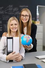 mitarbeiterinnen am schreibtisch mit globus und unterlagen