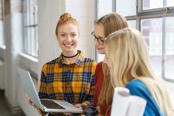 lächelnde studentinnen in der uni schauen auf ein notebook