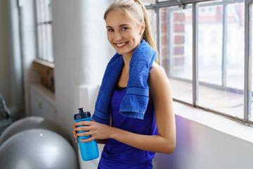 sportliche junge frau macht eine pause im fitness-studio