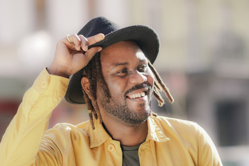 Cute African American man with rasta hair and beard and wearing yellow shirt