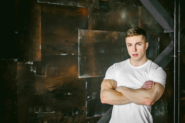 Young sexy men bodybuilder athlete, Studio portrait in a loft on the background of a stylized metal wall, a guy model in a white T-shirt and brown trousers, crossed his arms over his chest
