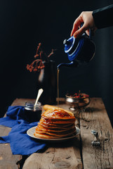 A stack of pancakes on a wooden vintage table, poured with melted honey. Black background. Still life. Toned picture