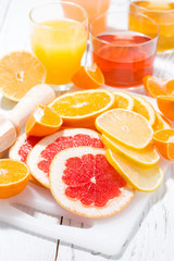 assortment of fresh citrus on a white board, vertical