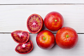 Several blood oranges ,whole and halved on a wooden table.top view