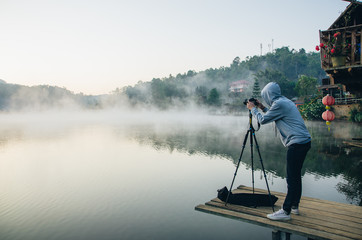 Photographer with foggy landscape