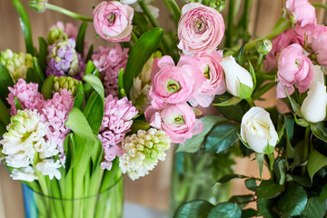 Bouquets of spring flowers on a wooden background. Roses and hyacinths on a wooden background