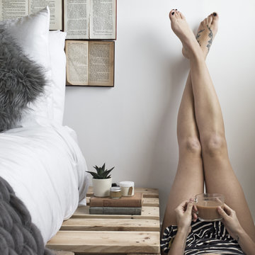 Young woman with crossed bare legs relaxing with hot drink
