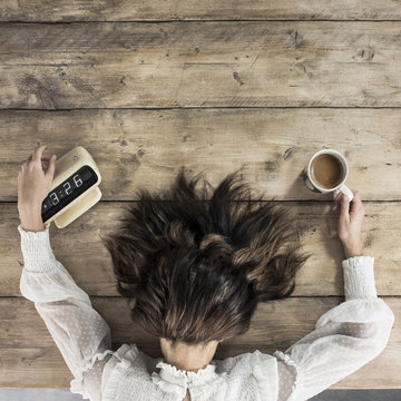 Tired young woman early morning alarm clock with coffee