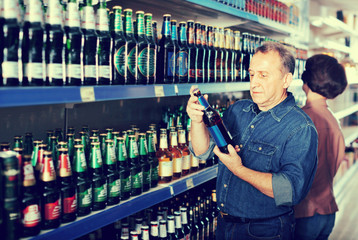Pensioner selecting a beer at the  store