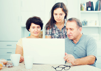 Cheerful adult daughter showing documents on laptop