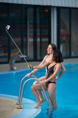 Two attractive females in bikini posing against the swimming pool with perfect aqua water and making selfie photo with monopod on the luxury resort