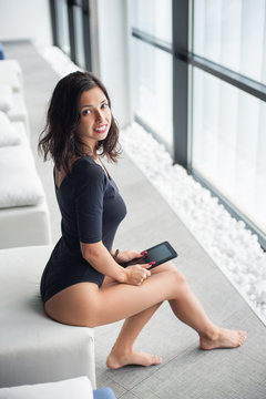Beauty woman in black bodysuit sitting on white lounger near big windows and holding tablet computer in hands at lounge zone in the spa resort