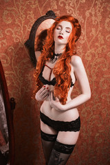 Portrait of a woman with long red curly hair in black lingerie and choker on her neck. Red-haired girl with pale skin, bright unusual appearance and red lips and a thin waist on background of a mirror